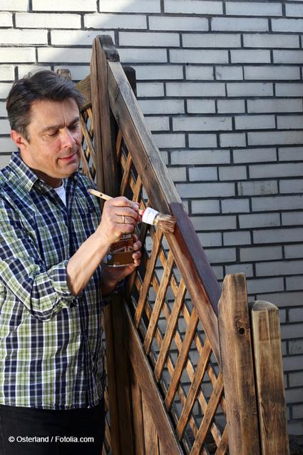Holzzaun, der mit einem Holzschutzmittelangestrichen wird als Beispiel für die Anwendung von Kupferoxid Nanopartikel als Holzschutz