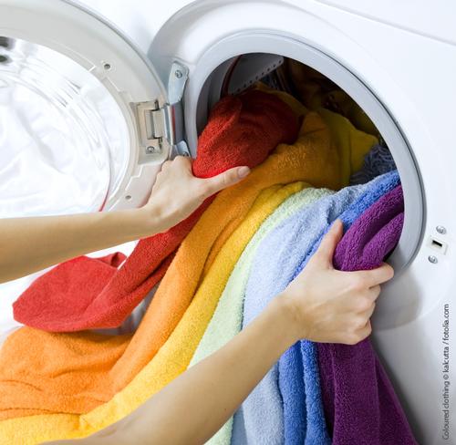 Geöffnete Waschmaschine, aus der Handtücher in den Farben des Regenbogens herausragen