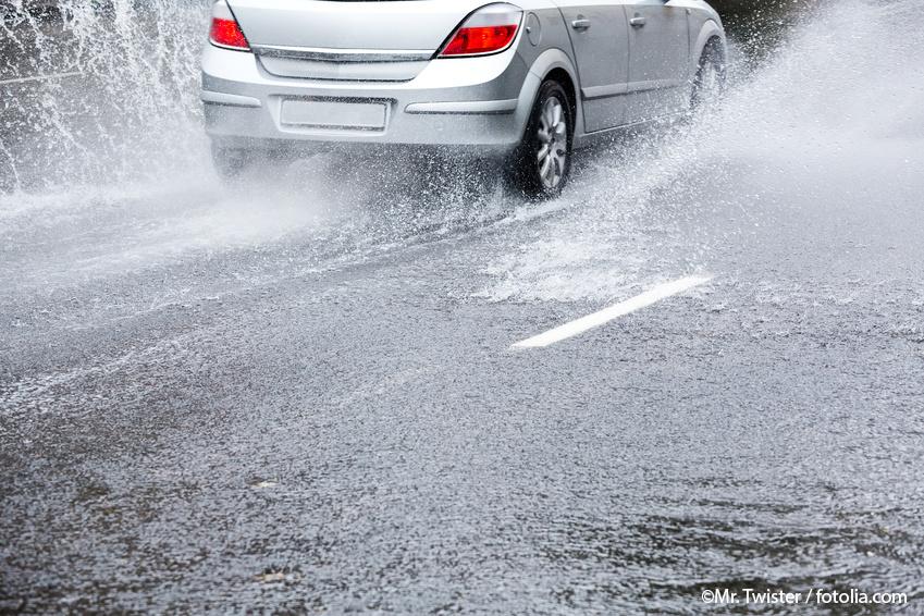 Mit wasser überflutete Straße, auf der ein fahrendes silbergraues Auto Spritzwasser erzeugt