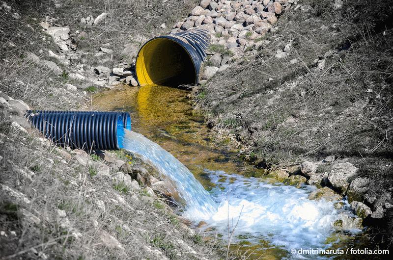 Außenaufnahme von zwei Abwasserrohren, aus denen Wasser in einen kleinen Bach geleitet wird